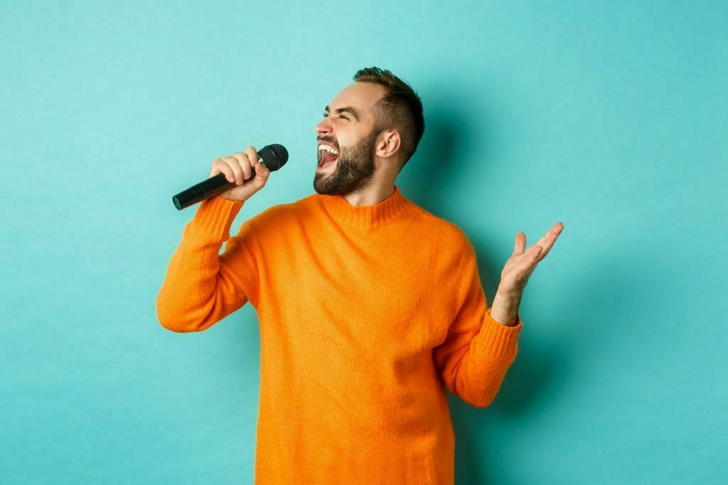 handsome adult man perform song, singing into microphone, standing against turquoise background